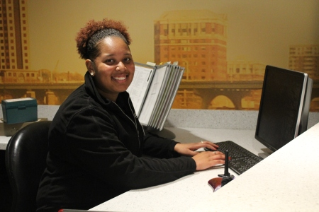 A smiling information assistant ready to help students