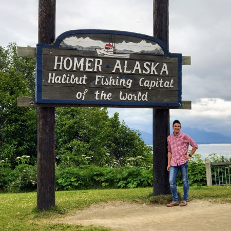 Dylan leans happily on the Homer, Alaska fishing capital of the world sign.