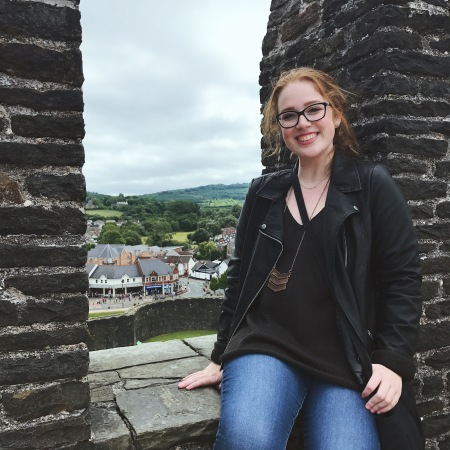 Emily sits on an aged brick wall overlooking a small town.