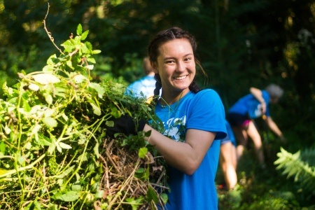 A cheerful volunteer smiles while moving vines from a local cemetery.