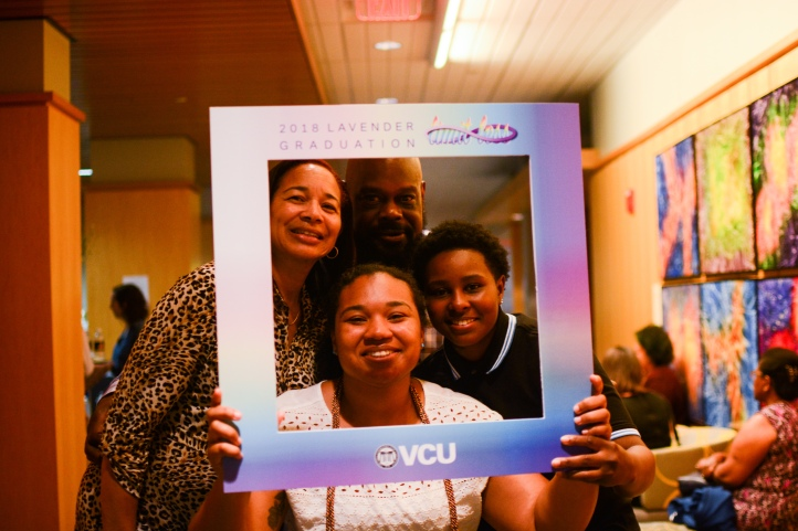 Lavender Graduation 2018 - Graudate celebrates with family and friends at reception by posing in photo frame.