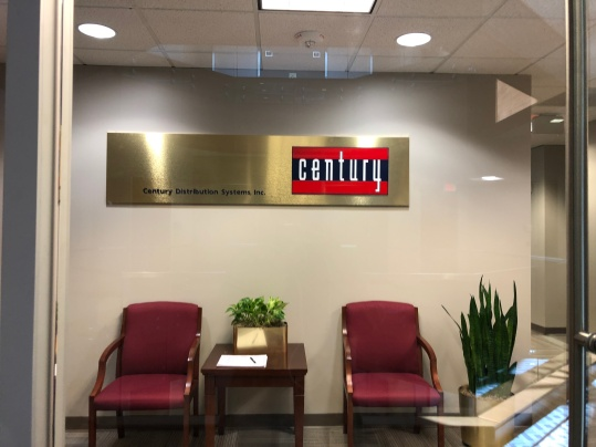 Century Distribution Systems, Inc. sign above chairs in a hallway