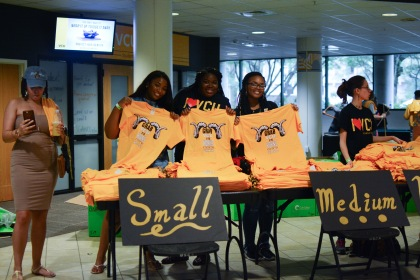 Students posing with VCU shirts inside the University Student Commons