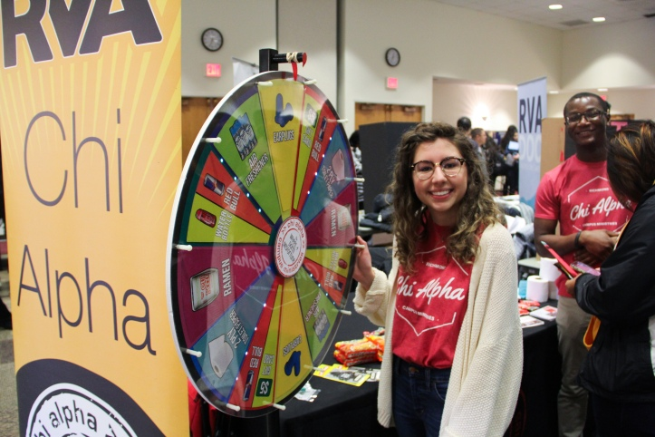 Student poses with spinning wheel at The Fair